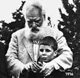 A black and white photo of Alexander Graham Bell helping a deaf boy learn sign language.